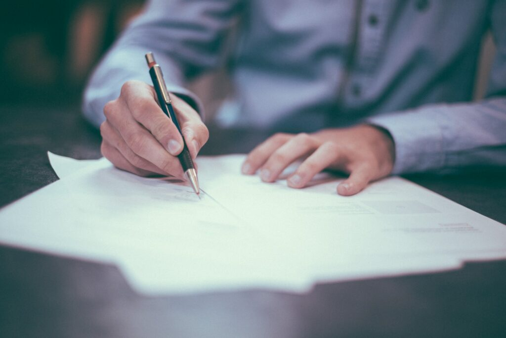 man writing project documents with pen